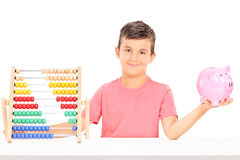 Boy holding a piggybank seated at a table with an abacus Royalty Free Stock Photos