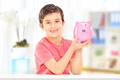 Boy holding a piggybank seated at a table, indoors Stock Photo