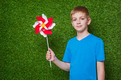 Boy holding pinwheel over grass Stock Photo