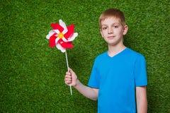 Boy holding pinwheel over grass Stock Photo
