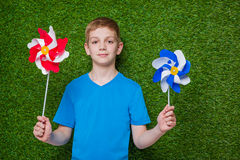 Boy holding pinwheels over grass Royalty Free Stock Photos