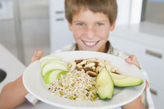 Boy holding plate of food Stock Photo