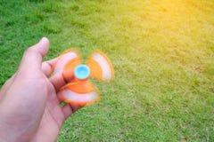 Boy holding play fidget spinners, Fidget spinner ogange colour s Stock Images