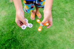 Boy holding play two fidget spinners, Fidget spinner white and o Stock Photo