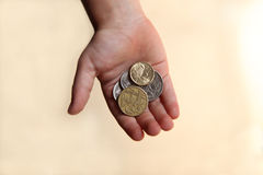 Boy holding pocket money. Boy holding some Australian coins in his open hand. Representing a childs pocket money or savings royalty free stock photography