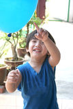 Boy holding & pointing at balloon Royalty Free Stock Image