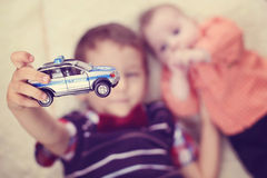 Boy holding a police car near baby brother Stock Image