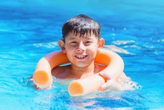 Boy holding on the pool noodle buoy for safety. Summertime holidays Royalty Free Stock Image