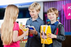 Boy Holding Popcorn While Siblings Talking At Stock Images
