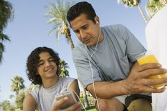 Boy holding portable mp3 father listening to music Royalty Free Stock Images
