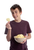Boy holding potato crisp and smiling Stock Photo