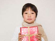 Boy holding a present. Boy wearing scarf holding a present Stock Photography