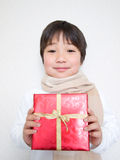 Boy holding a present. Boy wearing scarf holding a present Royalty Free Stock Photo