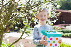 Boy holding a present. Cheerful smiling boy holding colorful present for mother's day or other celebration by the blooming tree at park at spring time Stock Photo