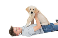 Boy holding puppy while lying over white background Royalty Free Stock Photo