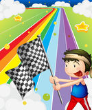 A boy holding a racing flag in the racing field Royalty Free Stock Photo
