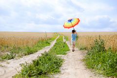 Boy holding rainbow umbrella standing on wide road Stock Photography