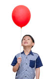 Boy holding red balloon over white background Stock Images