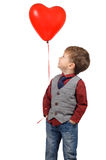 Boy holding red heart shaped balloon. Portrait of a cute smiling little boy holding a red heart shaped balloon isolated on white background Stock Photos