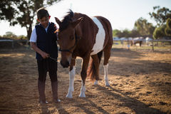 Boy holding the reins of a horse in the ranch Stock Images