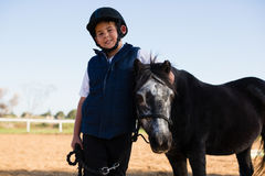 Boy holding the reins of a horse in the ranch Royalty Free Stock Image