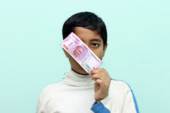 Boy holding 2000 rupee new Indian money in his hand. Royalty Free Stock Photography