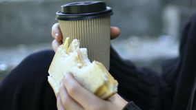 Boy holding sandwich and coffee, concept of hungry homeless abandoned children. Stock footage stock footage