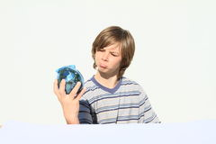 Boy holding saving pig full of money Royalty Free Stock Photography