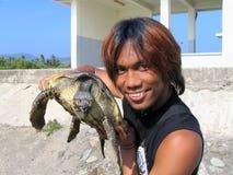 Boy holding sea turtle stock photography