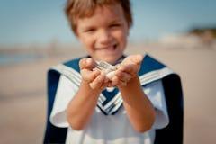 Boy holding seashells on palms Royalty Free Stock Photo