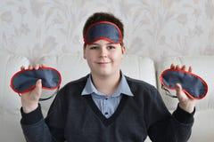 Boy holding a several masks for sleep Stock Photos