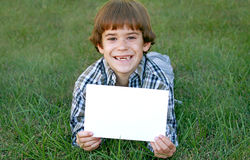 Boy Holding Sign. Boy Holding up a Blank Sign to Put Writing on royalty free stock photography