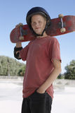 Boy Holding Skateboard In Skate Park. Portrait of confident teenage boy holding skateboard in skate park Stock Image