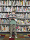 Boy Holding Stack Of Books In Library Royalty Free Stock Photography