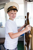 Boy holding the steering wheel of the ship Royalty Free Stock Photography