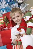 Boy Holding Stuffed Snowman In Front Of Christmas Tree Stock Image
