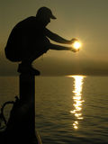 Boy holding the sun. Silhouette of young man who squatts on a post over lake royalty free stock image