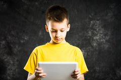 Boy holding a tablet device against dark background. Boy holding a white tablet device against dark background Royalty Free Stock Photos