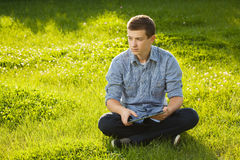 Boy holding tablet PC on green grass Royalty Free Stock Photography