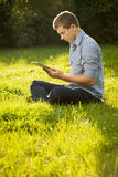 Boy holding tablet PC on green grass Stock Photos