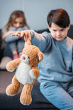 Boy holding teddy bear while offended girl sitting on sofa Royalty Free Stock Photos