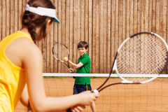 Boy holding tennis ball and racket, starting set. Sporty kid boy holding tennis ball and racket, starting set with his opponent on the clay court Royalty Free Stock Images