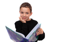 Boy holding a textbook. A content eight year old boy holds a textbook from his grade shool homework, on a white background Stock Image