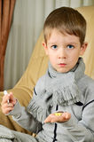 Boy holding a thermometer and pills vertical Stock Photo