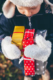 Boy holding three gifts with winter gloves Royalty Free Stock Photo