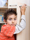 Boy holding on to cupboard door Stock Photography