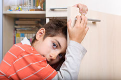 Boy holding on to cupboard door Royalty Free Stock Images