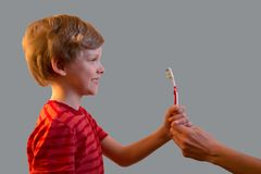 The boy is holding a toothbrush in his hand. Isolated. The boy is holding a toothbrush in his hand. The photo shows the mother`s hand, which feeds the brush to Stock Image