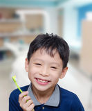 Boy holding toothbrush and smiles Stock Images