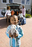 Boy (6-8) holding toy in driveway, family loading luggage into car in background, smiling, portrait Stock Photos